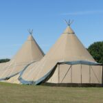 Two large tepees set up for event on farmland