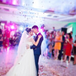 Touching and emotional first dance of the couple on their wedding with confetti and colorful lights on the background.