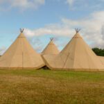 Three large tepees set up for a wedding event on farmland