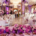 Look from behind dinner table decorated with garland of pink and white flowers at large dinner hall